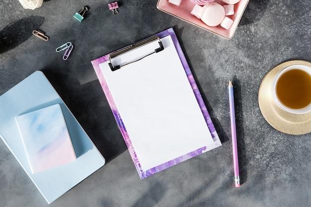 Plat leggen van kantoorbenodigdheden met kopje thee met marshmallow en laptop Premium Foto