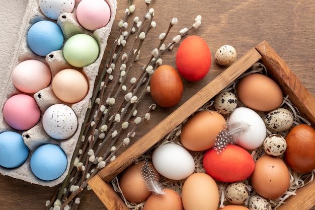 Plat leggen van kleurrijke eieren voor pasen in doos en karton met bloemen Gratis Foto