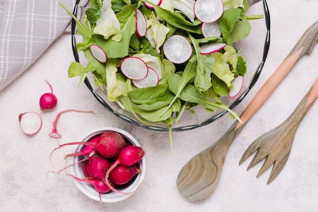 Plat leggen van kom salade met radijs Gratis Foto