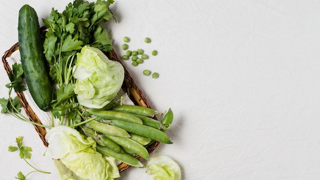 Plat leggen van komkommer en assortiment van groenten in de mand Gratis Foto