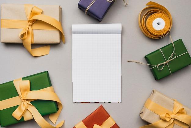 Plat leggen van laptop mock-up met kerstcadeaus Gratis Foto