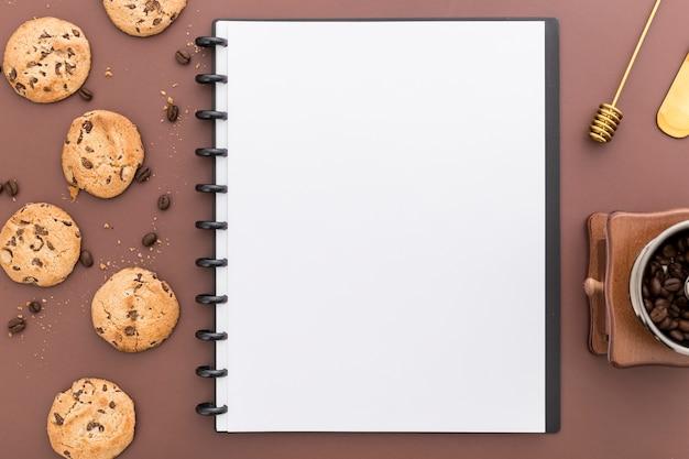 Plat leggen van lege menu notebook met cookies Gratis Foto