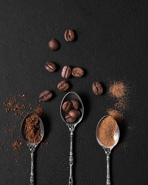 Plat leggen van lepels gevuld met geroosterde koffiebonen en poeder Gratis Foto