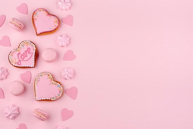 Plat leggen van macarons en hartvormige koekjes voor valentijnsdag Gratis Foto