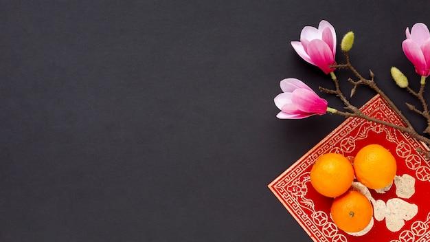 Plat leggen van magnolia en mandarijnen nieuw chinees jaar Gratis Foto
