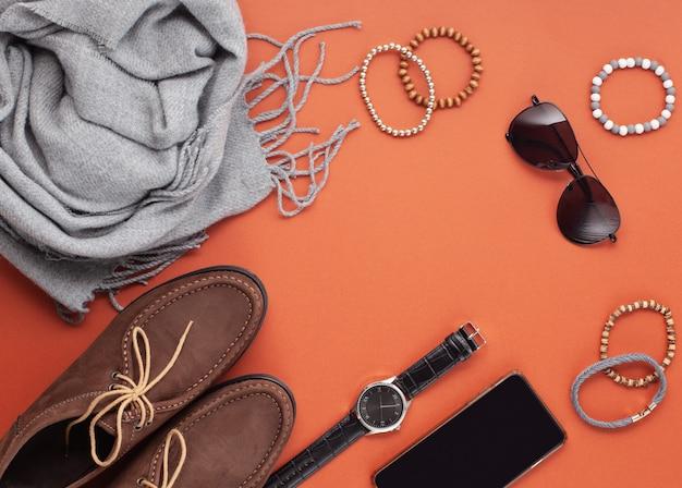 Plat leggen van mannenaccessoires met schoenen, horloge, telefoon, oortelefoons, zonnebril, sjaal over de oranje achtergrond Premium Foto