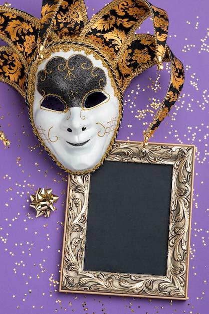 Plat leggen van masker voor carnaval met glitter en frame Gratis Foto