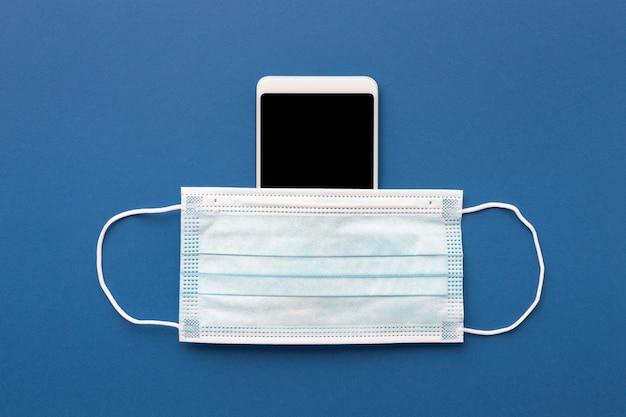 Plat leggen van medisch masker met smartphone Gratis Foto