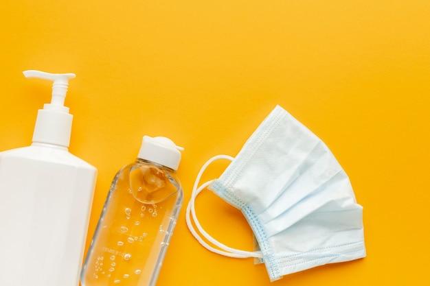 Plat leggen van medisch masker met vloeibare fles en handdesinfecterend middel Gratis Foto