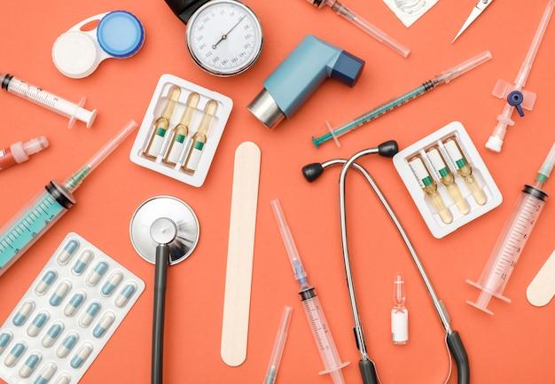 Plat leggen van medische hulpmiddelen op gekleurde achtergrond Premium Foto