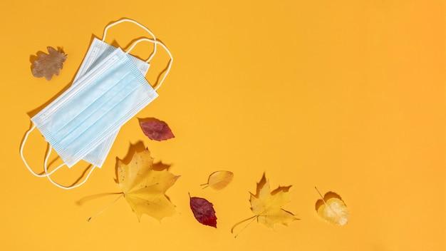 Plat leggen van medische maskers met herfstbladeren en kopie ruimte Gratis Foto
