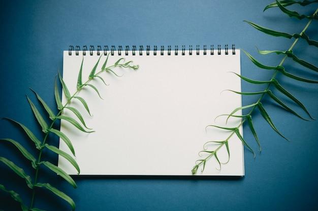 Plat leggen van minimaal werkruimtebureau met notitieboekje en groene installatie, op diepe blauwe toon Premium Foto