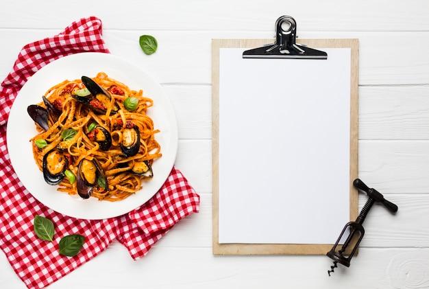 Plat leggen van mosselen pasta met klembord Gratis Foto