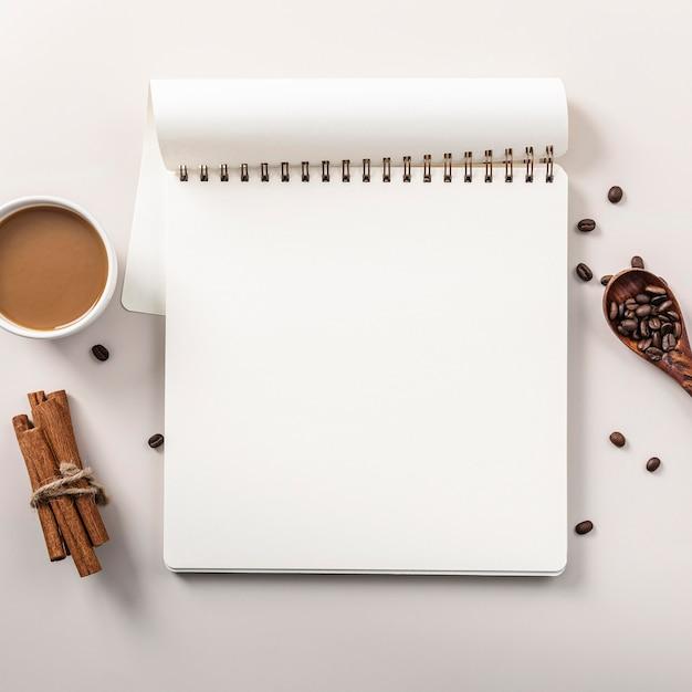 Plat leggen van notebook met koffiekopje en kaneelstokjes Gratis Foto