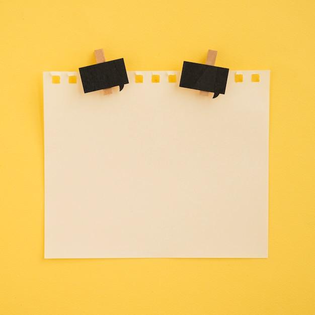 Plat leggen van notitie en paperclips met gele achtergrond Gratis Foto