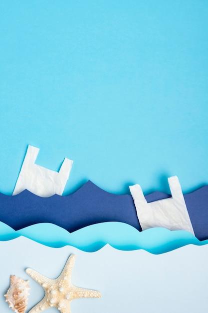 Plat leggen van papieren oceaangolven met plastic zakken en zeesterren Gratis Foto