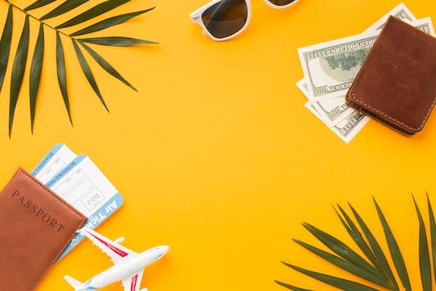 Plat leggen van paspoorten en geld met vliegtickets en beeldje Gratis Foto