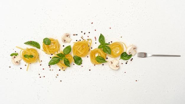 Plat leggen van pasta champignons en basilicum op effen achtergrond Gratis Foto