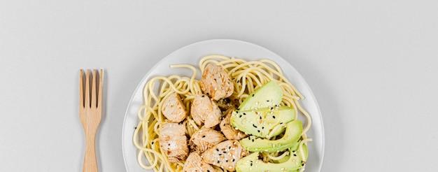 Plat leggen van pasta met vlees en avocado op plaat Gratis Foto