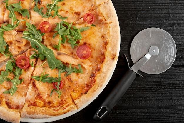 Plat leggen van pizza met rucola en cherry tomates op houten tafel Gratis Foto