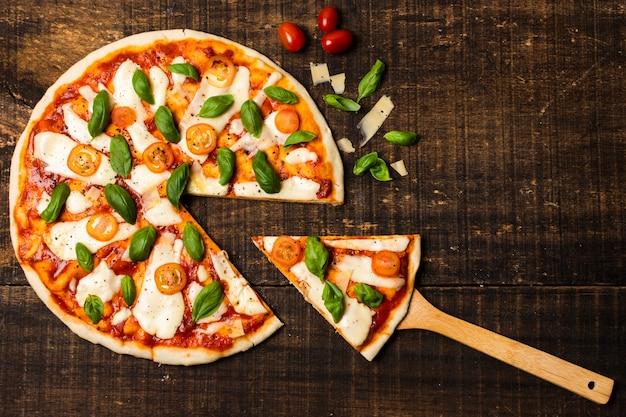 Plat leggen van pizza op houten tafel Gratis Foto