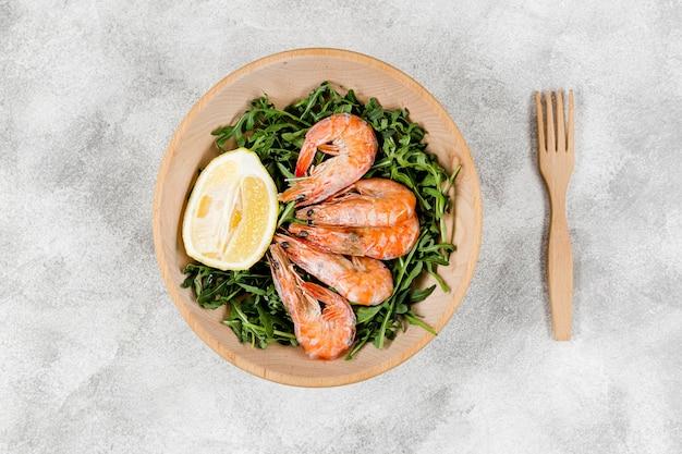 Plat leggen van plaat met garnalen op salade met citroen Gratis Foto