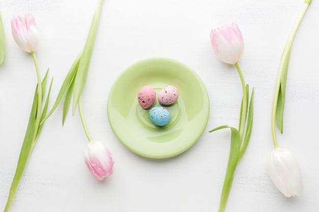 Plat leggen van plaat met kleurrijke paaseieren en mooie tulpen Gratis Foto