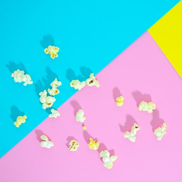 Plat leggen van popcorn op kleurrijke achtergrond Gratis Foto