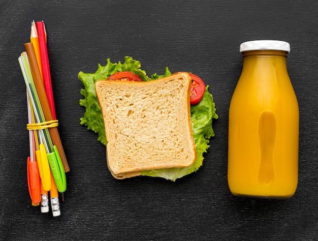 Plat leggen van schoolbenodigdheden met sandwich en potloden Premium Foto