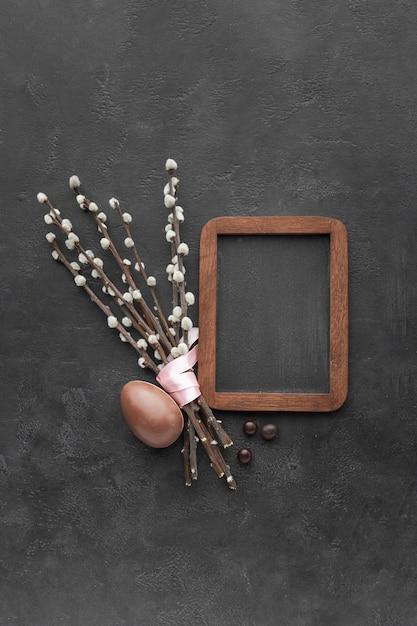Plat leggen van schoolbord met chocolade paasei en bloemen Gratis Foto