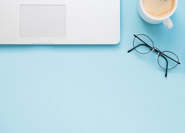 Plat leggen van schoon bureau met blauwe achtergrond Gratis Foto