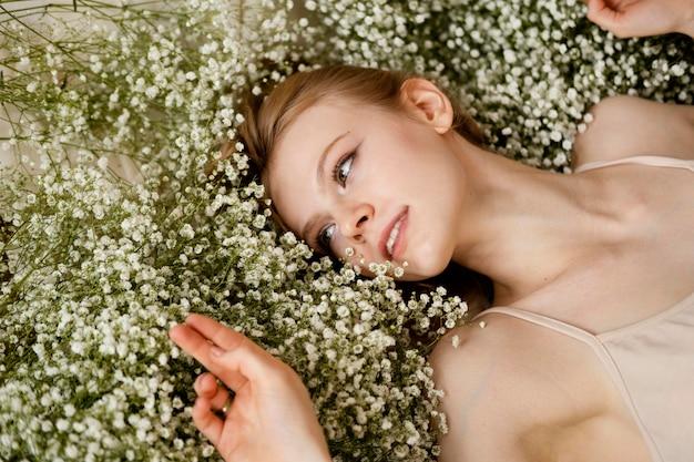 Plat leggen van smiley vrouw poseren met lentebloemen Premium Foto