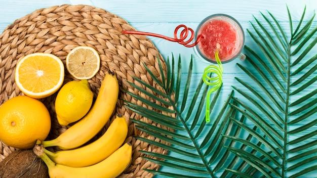 Plat leggen van smoothie en fruit op houten tafel Gratis Foto