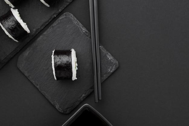 Plat leggen van sushi roll op leisteen met stokjes Gratis Foto