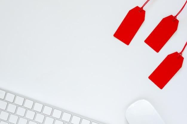 Plat leggen van toetsenbord en muis met rode prijskaartje op witte achtergrond voor cyber monday online verkoopconcept. Premium Foto