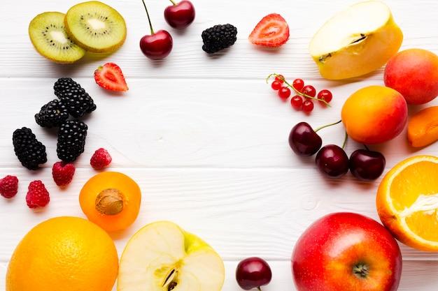 Plat leggen van verse bessen en fruitkader Gratis Foto