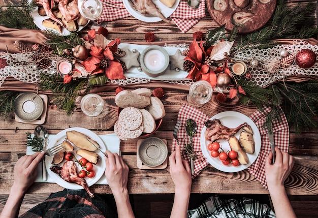 Plat leggen van vriendenhanden die samen eten en drinken. bovenaanzicht van mensen die partij hebben, verzamelen, vieren samen aan houten rustieke tafel Premium Foto