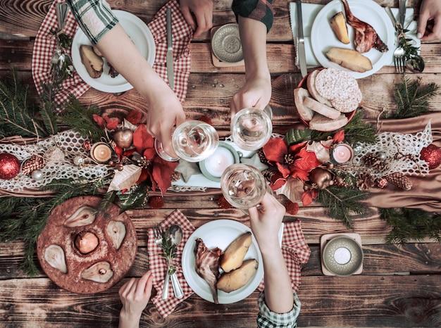 Plat leggen van vriendenhanden die samen eten en drinken. bovenaanzicht van mensen die partij hebben, verzamelen, vieren samen aan houten rustieke tafel Gratis Foto