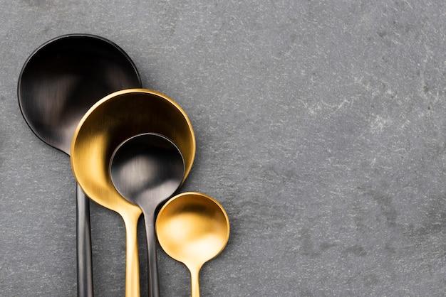 Plat leggen van zwarte en gouden lepels met kopie ruimte Gratis Foto