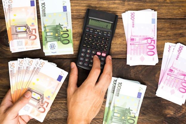 Plat leken man geld tellen met calculator Gratis Foto