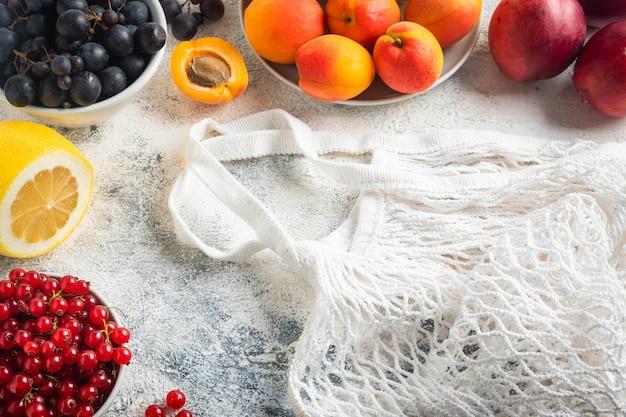 Plat liggend, bessen, fruit en zakgaas op grijs Premium Foto