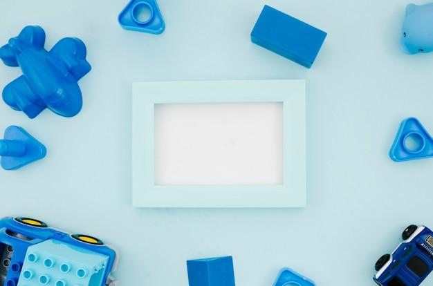 Plat liggend kinderspeelgoed met een modelframe Gratis Foto
