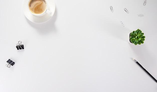 Plat liggende, bovenaanzicht kantoor tafel bureau. werkruimte met leeg klembord, kantoorbenodigdheden, potlood, groen blad en koffie Premium Foto