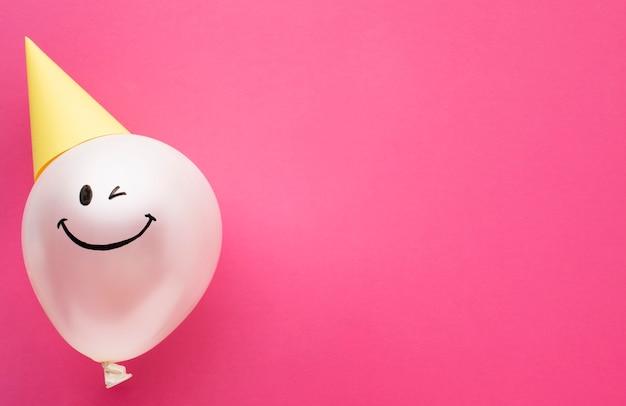 Plat liggende frame met ballon en feestmuts Gratis Foto