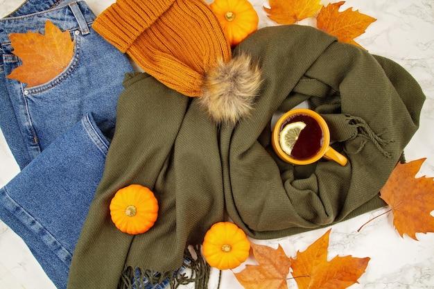 Plat liggende herfstsamenstelling met herfstbladeren, pompoenen, warme kop thee en een warme wollen sjaal en muts Premium Foto