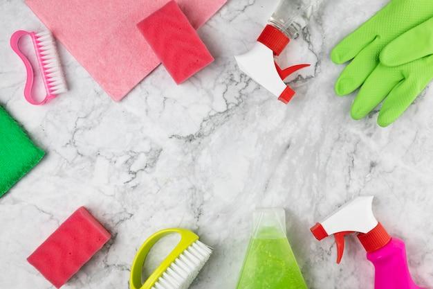 Plat liggende opstelling met schoonmaakartikelen en marmeren tafel Gratis Foto
