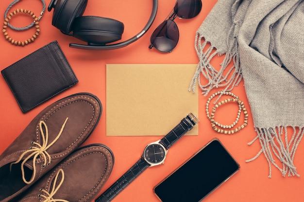 Plat met mannenaccessoires met schoenen, horloge, telefoon, oortelefoons, zonnebril, sjaal over de sinaasappel Premium Foto