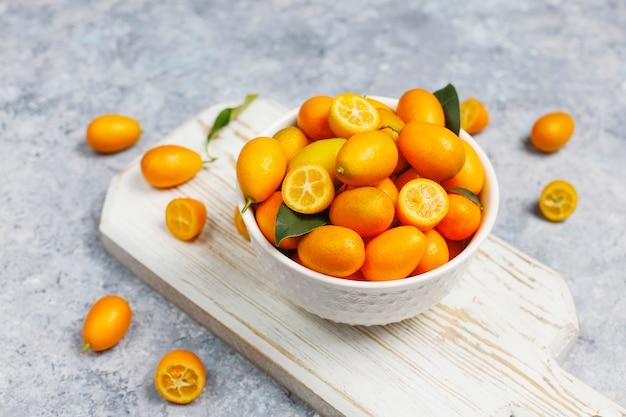 Plat van kumquats op een betonnen ondergrond Gratis Foto