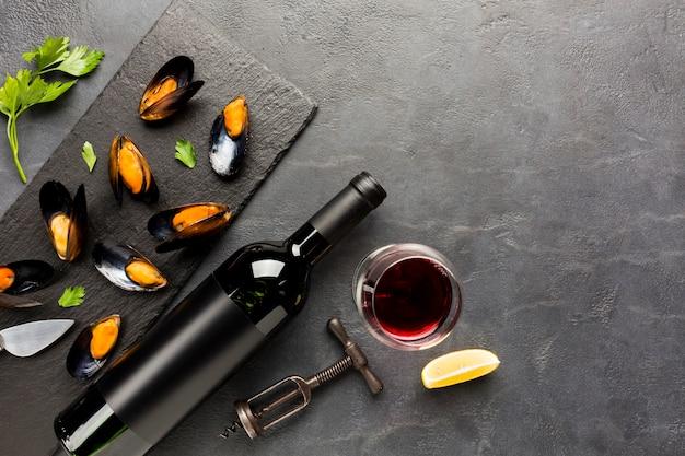 Platgelegde gekookte mosselen en wijn met copyspace Gratis Foto
