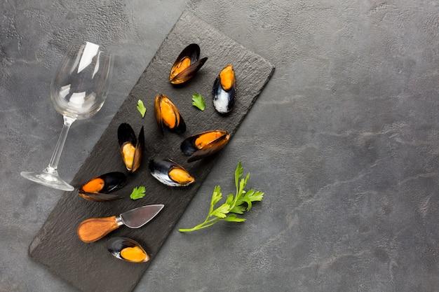 Platgelegde gekookte mosselen op leisteen met copyspace Gratis Foto